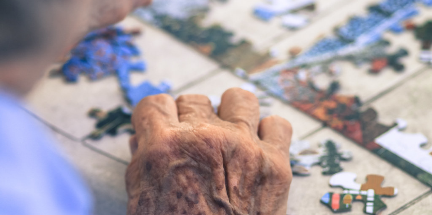 Elderly man working a jigsaw puzzle